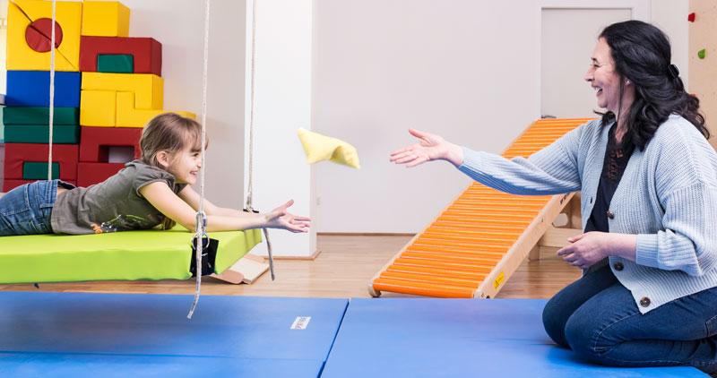 Ergotheapiepraxis in Linz Urfahr _ Ergotherapeutin mit Kind auf Therapieschaukel